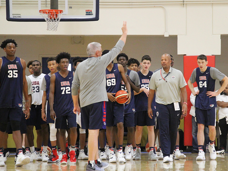 Athletes look on as USA head coach Don Showalter puts in a play.