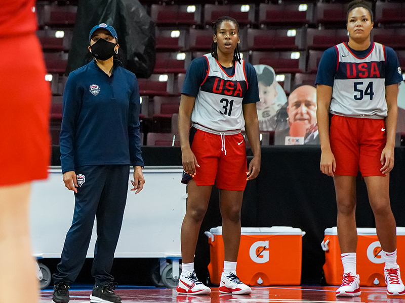 USA head coach Dawn Staley watches on the sideline alongside Ariel Atkins (center) and Napheesa Collier.