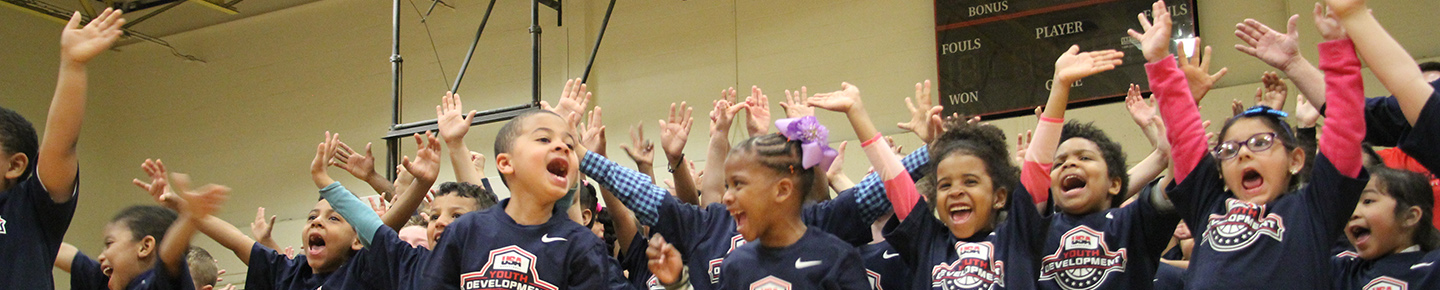kids waving and cheering at a USA Basketball youth development event