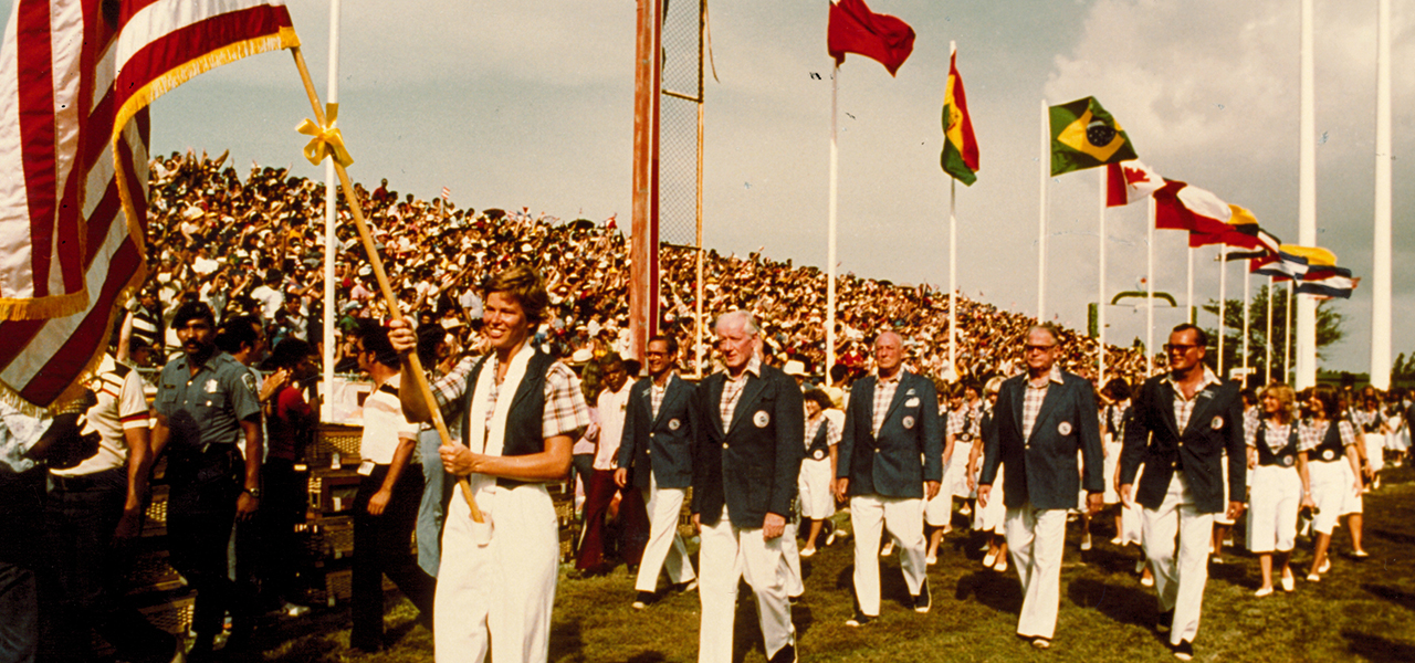 Ann Meyers carries the U.S. flag ahead of the USA delegation at the 1979 Pan American Games Opening Ceremony.